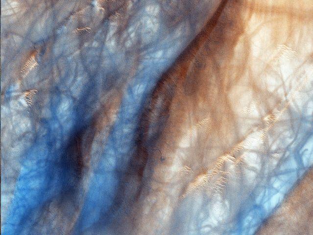 Diablos de polvo: Estos torbellinos de arena desplazan la fina capa de polvo de la superficie marciana dejando expuesta una región oscura. Las huellas azules corresponden a las marcas que deja a su paso este fenómeno.