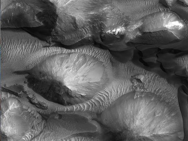 Juventae Chasma:<br /> Este enorme cañón de aproximadamente 250 kilómetros de largo y 100 kilómetros de ancho, al norte de Valles Marineris, está parcialmente cubierto de dunas.