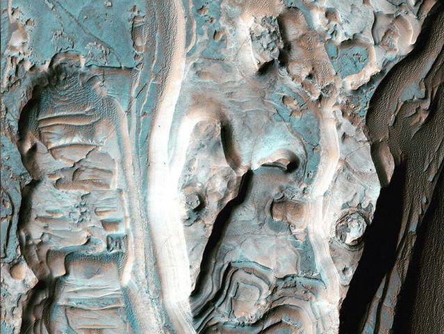 Capas de erosión en un cráter: El depósito que se observa forma una serie de crestas debido al poder erosivo del viento.